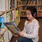 Student reading book next to library shelves